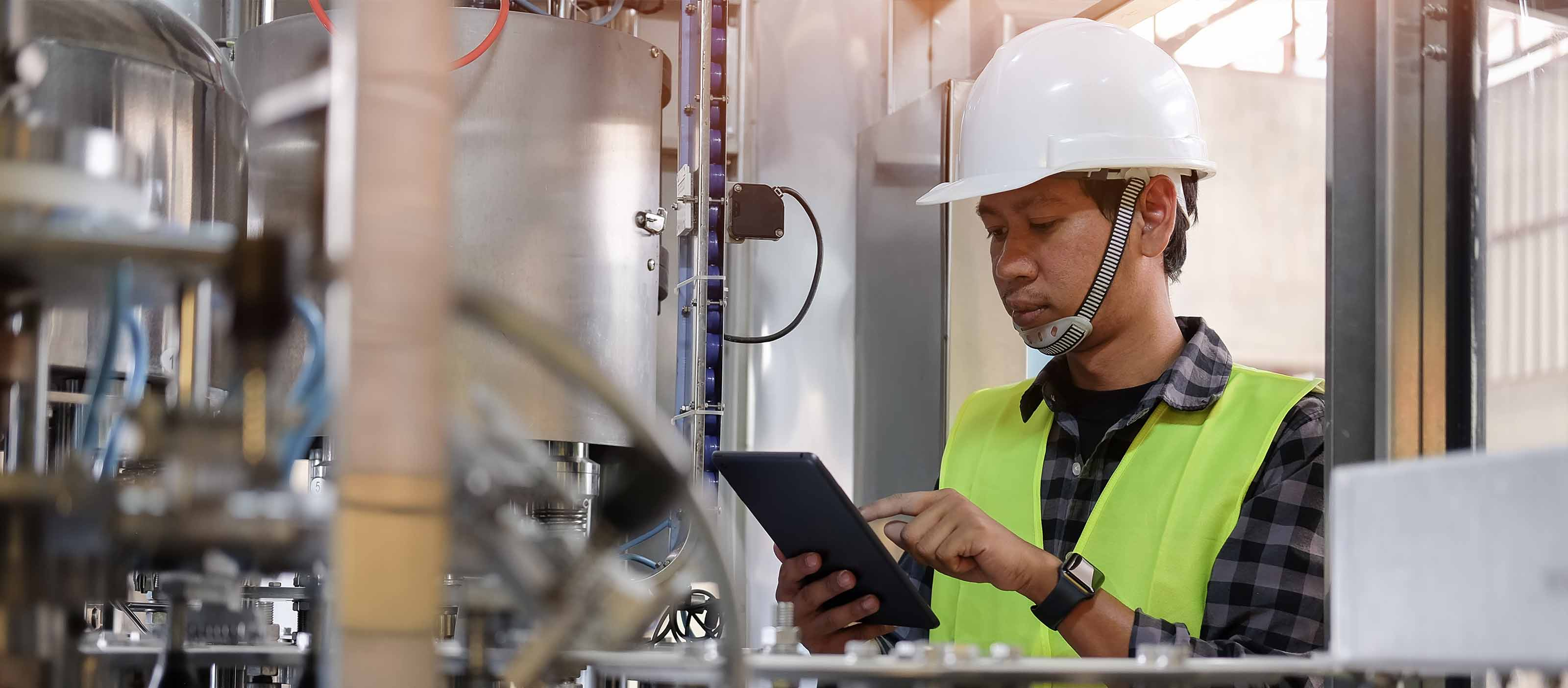 Industrial engineer checking operational data with GE Digital software
