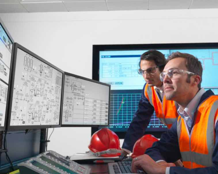 Engineers using GE Digital industrial software in a control room