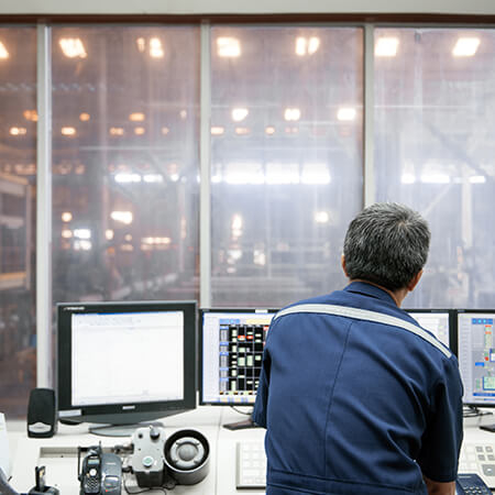 Engineer in control room using GE Digital industrial software with predictive analytics