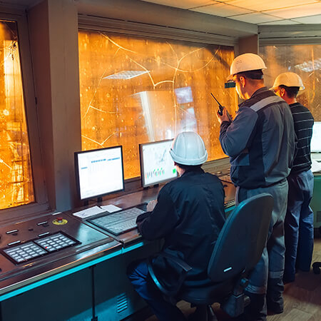 Engineer in control room using GE Digital industrial software and predictive analytics