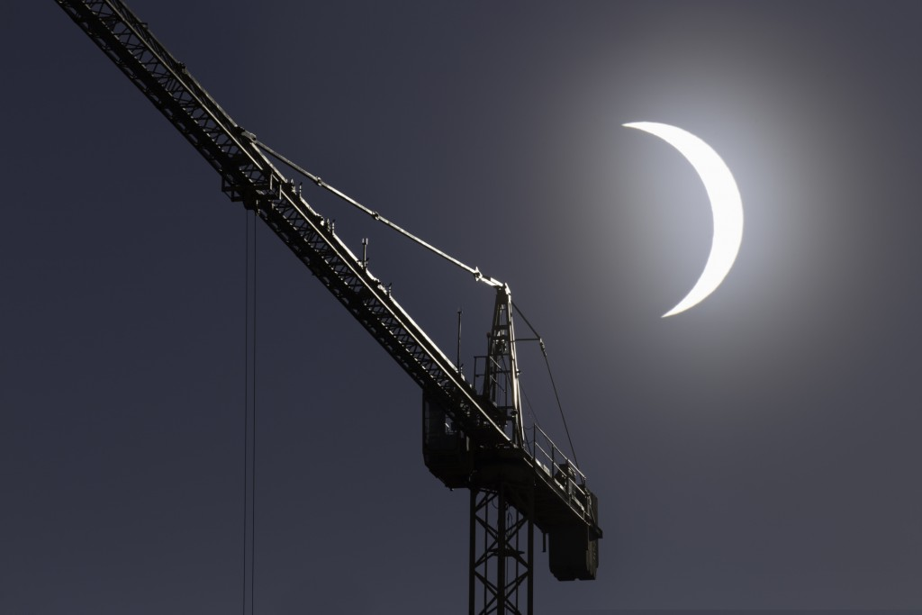 Picture of solar eclipse with construction crane in the foreground