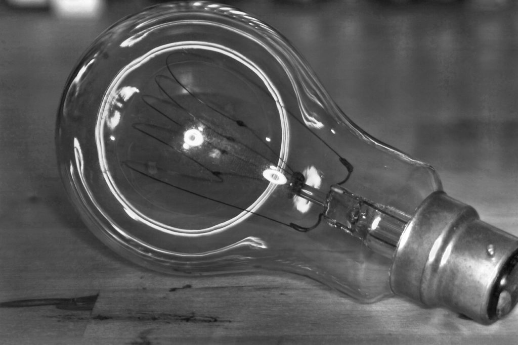 A Black and white shot of a an old carbon filament bulb.