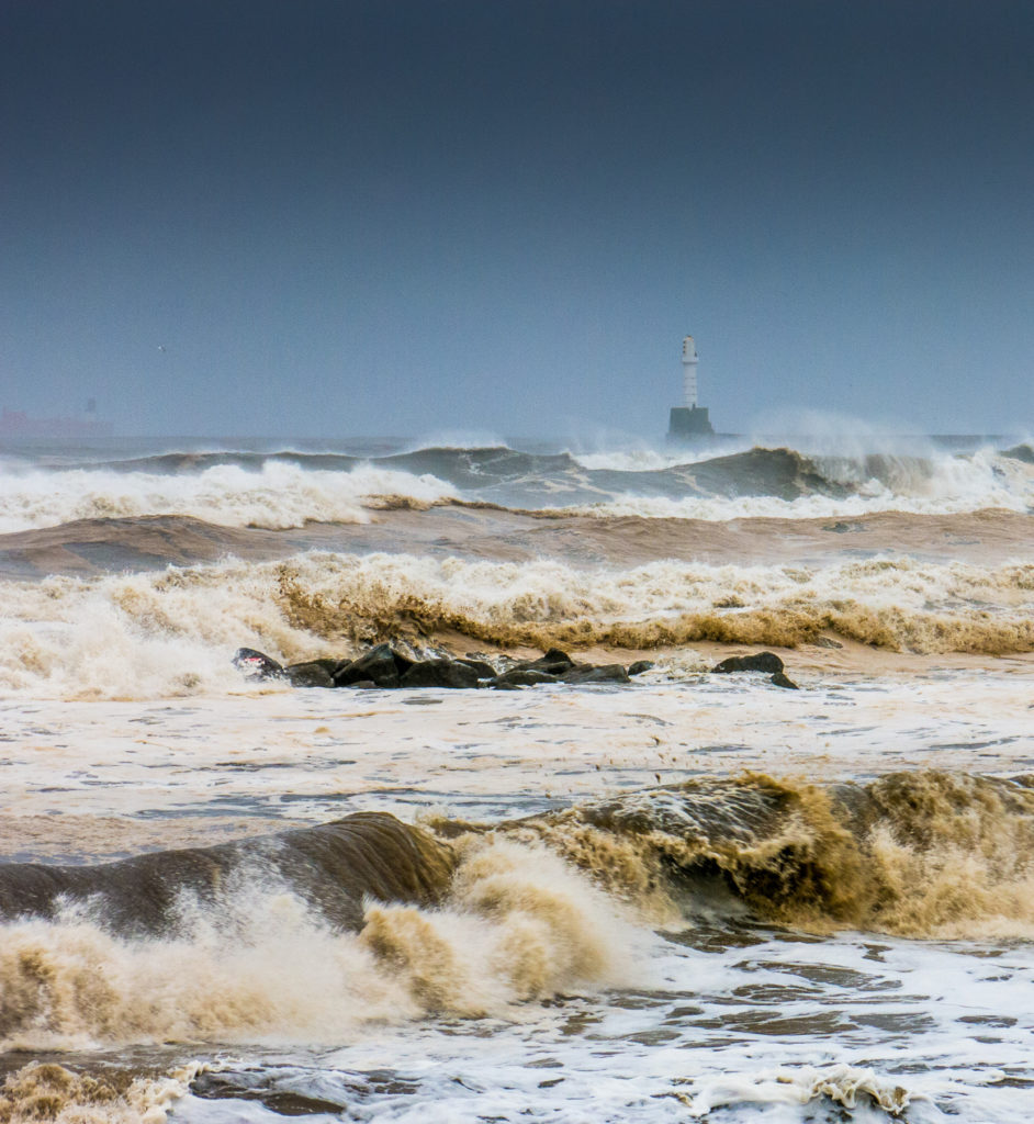 Extreme weather during Fall at Aberdeen beach, Scotland, UK, causes large waves to batter the shore. With Aberdeen lighthouse in the background against the North Sea. The sea looks aggressive and unforgiving.