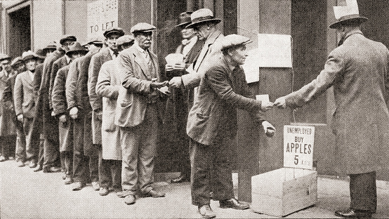 (A line of unemployed men buy apples for 5 cents during the Great Depression of America. From The Literary Digest, published 1930. Courtesy Getty Images.)