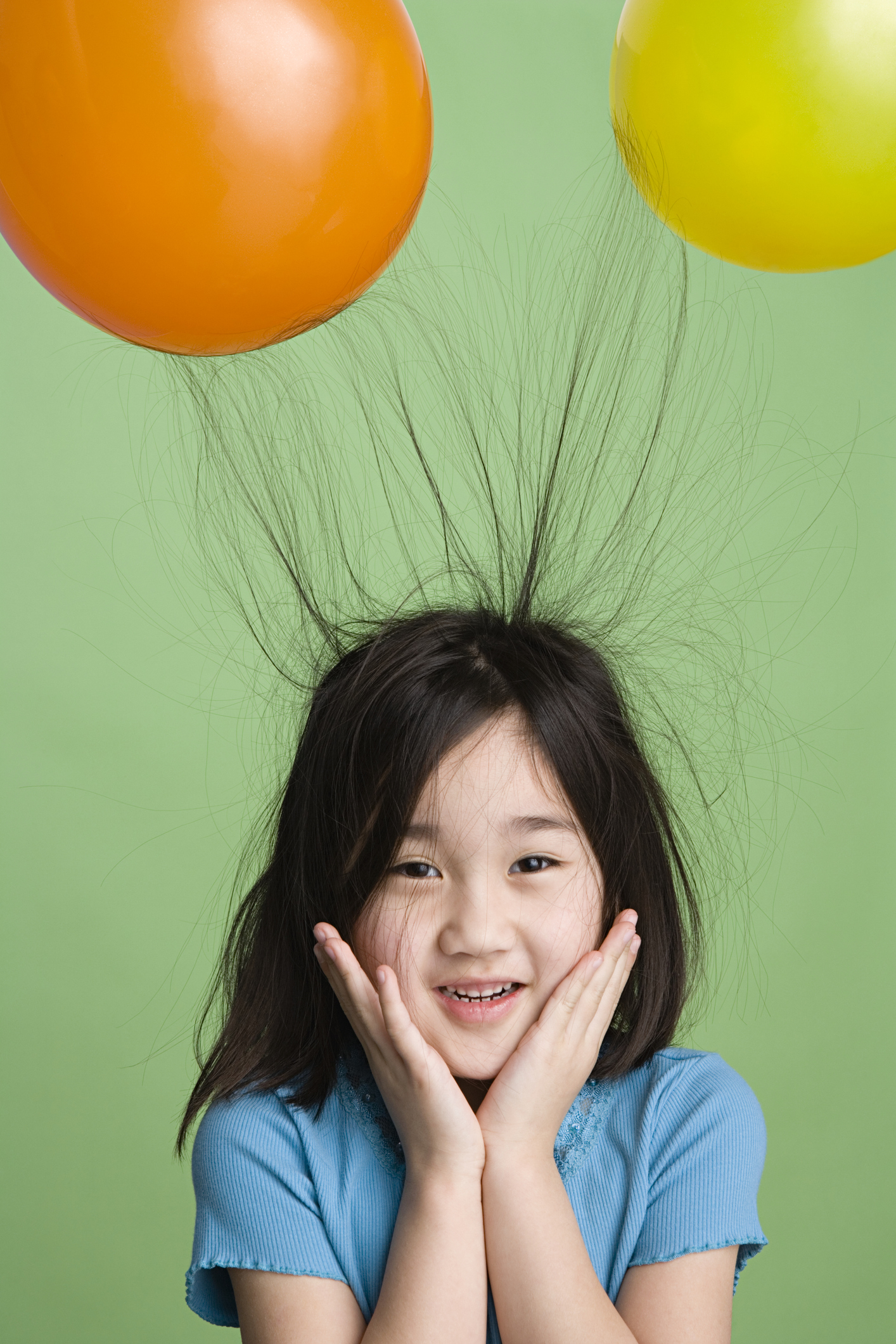 Static electricity caused by balloons makes a kid's hair stand up