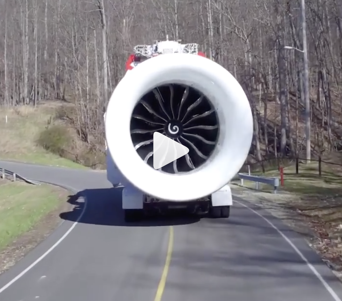Screenshot of the GE9X being transported on a two-lane road